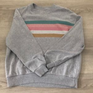 A gray crewneck with colourful stripes